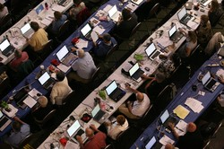 Photo of rows of people seated at tables in front of laptops